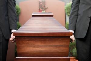 Pracownicy zakładu pogrzebowego elegia niosą trumnę